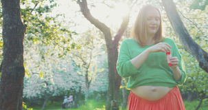 Merry Pregnant Woman among Blooming Trees. Steadicam shot of pregnant woman walking in garden among blooming trees and blowing soap bubbles stock video