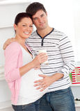 Merry pregnant woman holding a glass of milk Royalty Free Stock Image