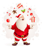 Merry Santa Claus juggles with Christmas gifts and sweets as magician Royalty Free Stock Photos