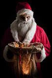 Merry scary christmas. A scary looking santa holding  a glowing present bag Royalty Free Stock Image