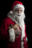 Merry scary christmas. A scary looking santa holding  a glowing present bag Royalty Free Stock Photo