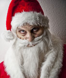 Merry scary christmas. A scary looking santa holding  a glowing present bag Royalty Free Stock Photography