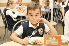 Merry schoolboy Sitting At Table In School Cafeteria Eating Meal. drinking juice - Russia, Moscow, the first High School, the firs royalty free stock photos