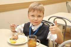 Merry schoolboy Sitting At Table In School Cafeteria Eating Meal. drinking juice and shows thumbs up - Russia, Moscow, the first H Stock Photography