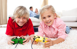 Merry siblings playing video game lying. On the floor in the living-room with parents in the background Stock Photos