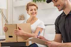 Merry smiling man delivers parcel royalty free stock photography