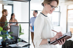 Merry smiling manager making notes. Happy female worker wearing glasses is standing in office and writing at notebook with smile. Coworkers are discussing Royalty Free Stock Images