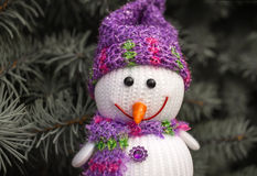Merry snowman looks smiling .background of Christmas tree Stock Image