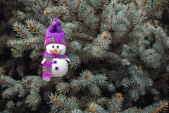 Merry snowman looks smiling on the background of Christmas tree Royalty Free Stock Images