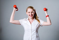 Merry successful businesswoman with raised dumbbells. Royalty Free Stock Photos