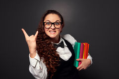 Merry teacher with books showing sign of the horns Royalty Free Stock Photography
