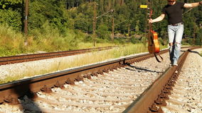 Merry teenager balancing with guitar on the railways dressed ripped denim walk stock video