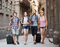 Merry travelers walking the street Royalty Free Stock Images