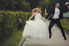 Merry wedding couple jumps on the road Royalty Free Stock Images