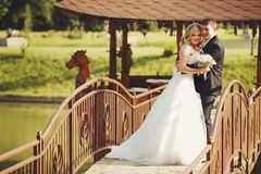 Merry wedding couple stands on a wooden bridge Royalty Free Stock Photos