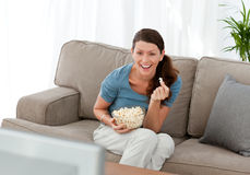Merry woman eating pop corn Stock Image