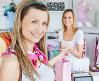 Merry woman getting shopping bags from saleswoman Stock Image