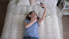 Merry woman into headphones enjoy music and takes selfie photo on mobile phone while relaxing on bed. Top view stock footage