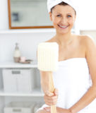 Merry woman holding a brush smiling at the camera. In the bathroom Stock Image