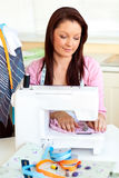 Merry woman sewing at home. In the kitchen Stock Image