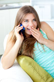Merry woman talking on phone sitting on a sofa Royalty Free Stock Photo