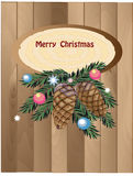 Merry wood background. Branch of christmas tree with cones and xmas ball on the wood background Royalty Free Stock Photo