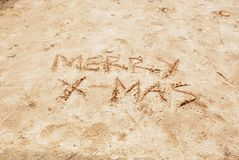 Merry X-mas written on beach sand Royalty Free Stock Images