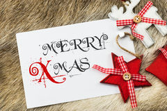 Merry Xmas card with text. Merry Christmas text written as Merry Xmas in black and red on white background. Seasons greetings postcard image design. Reindeer and Stock Photos