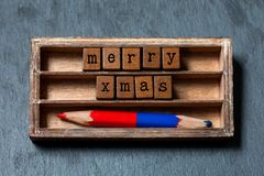 Merry Xmas concept. Vintage box, wooden cubes phrase with old style letters, red blue pencil. Gray stone textured. Background. Close-up, up view, soft focus Stock Image