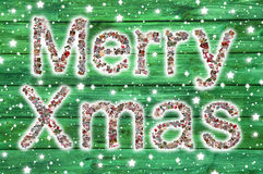 Merry Xmas greetings with text on green wooden background - lett Stock Image