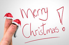 Merry Xmas hand writing with red mark on a transparent board and a Lovely Couple Fingers.  stock photography