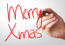 Merry Xmas hand writing with a red mark on a transparent board. Motivation hand writing with a blue mark on a transparent board royalty free stock images
