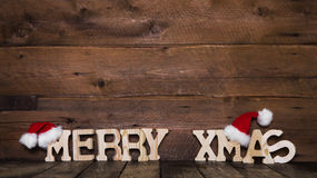 Merry Xmas letters on wooden background: idea for a greeting car. D with red santa hats Royalty Free Stock Image
