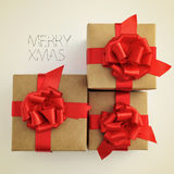 Merry xmas. Picture of some gifts with a red ribbon bow and the sentence merry xmas on a beige background, with a retro effect Royalty Free Stock Photos