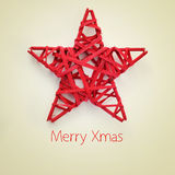 Merry xmas. A red christmas star and the sentence merry xmas on a beige background, with a retro effect Royalty Free Stock Photo