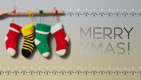 Merry Xmas text invitation card. Hanging Christmas socks on gradient gray beige background. Colorful stocking decoration. Poster. Wooden plank and colored ropes Royalty Free Stock Images