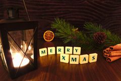 Merry Xmas words with flashlight candle, star, pine branch, cinnamon and orange Stock Images