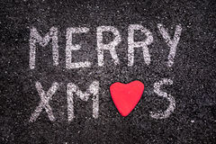 Merry xmas written on asphalt road, red stone in the shape of a heart Stock Photos