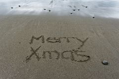 Merry Xmas written in the sand with wet sand behind royalty free stock photos