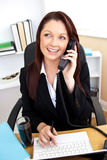 Merry young businesswoman talking on phone Royalty Free Stock Photography