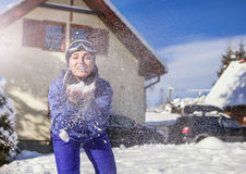Merry young female blows snow into camera on the cute mountain house background Royalty Free Stock Photography