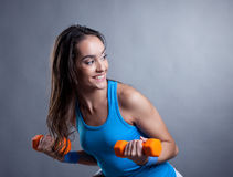 Merry young woman exercising with dumbbells Royalty Free Stock Images