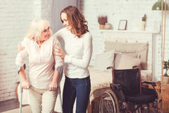 Merry young woman helping disabled old lady at home. On the way to dreams. Cheerful happy young women standing in the bedroom and taking care of old disabled Royalty Free Stock Photos