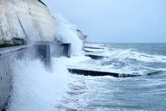 Mers agitées se brisant contre le mur de mer de Brighton avec des falaises derrière photos libres de droits