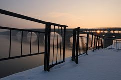 Merto subway Bridge at winter sunrise, viewed from embankment of the Dnieper River. The embankment is covered with snow Stock Photo
