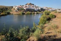 MERTOLA, PORTUGAL: Vista geral da vila fortificada do banco oposto do rio Guadiana imagem de stock