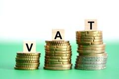mervärdeskatt eller moms på bunt av mynt som föreslår skattförhöjning royaltyfri fotografi