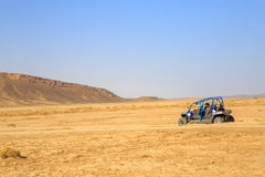 Merzouga Marocko - Februari 24, 2016: den tillbaka sikten på den blåa polstjärnan RZR 800 med den är piloter i den Marocko öknen  Royaltyfria Bilder