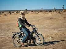 Merzouga, Marokko - December 04, 2018: Berber op een motorfiets, in het midden van de woestijn stock foto