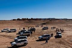 Merzouga, Marokko - December 05, 2018: kudde van toeristen in het midden van de woestijn met een kleine stad op de achtergrond royalty-vrije stock foto